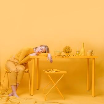 Woman sleeping on table in a yellow scene