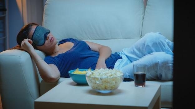 소파에 누워 있는 tv 앞에서 눈을 가리고 자는 여자. 피곤하고 지친 외로운 잠옷을 입은 외로운 잠자는 텔레비전 앞 소파에서 잠이 들고 영화를 보면서 눈을 감습니다.