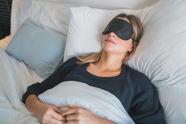 Женщина спит с маской сна.