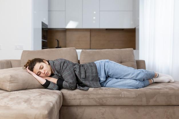 Женщина спит дома на диване, отдыхая после работы