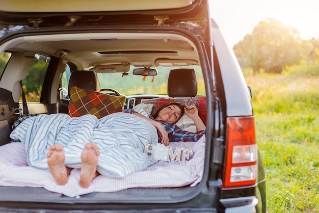 Woman sleeps comfortably her car luggage compartment nature summer under blanket