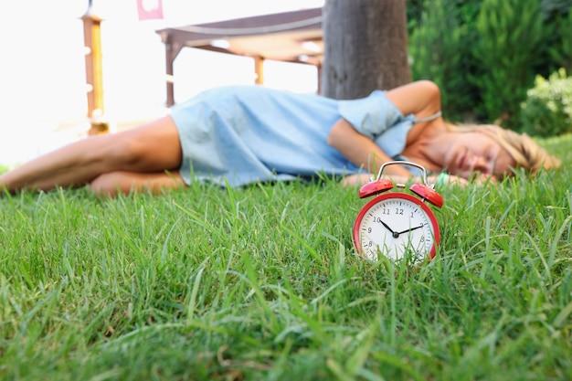 여자는 알람 시계 꿈과 환상 개념 옆 잔디에서 잔다