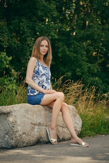 Woman in sleveless blouse and denim skirt having rest at country recreation area, enjoying fresh air and calmness