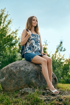 Woman in sleveless blouse and denim skirt having rest at country recreation area, sitting on large rock