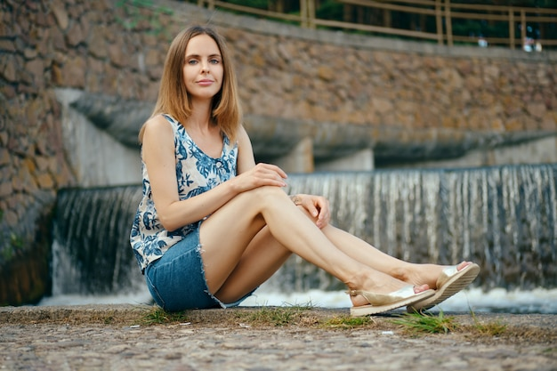 Woman in sleveless blouse and denim skirt having rest at country recreation area, sitting near artificial waterfall