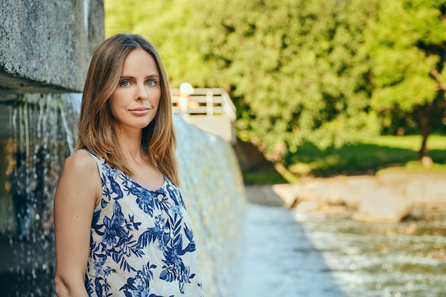 Woman in sleveless blouse having rest at country recreation area, standing near artificial waterfall