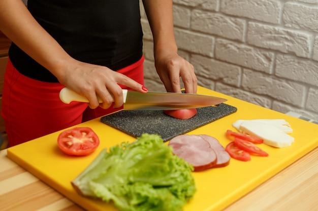 Woman slice tomato