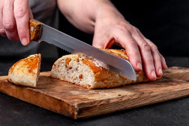 Женщина ломтиками домашнего хлеба из цельнозерновой муки с зернами льна и кунжута на деревянной доске на темном столе