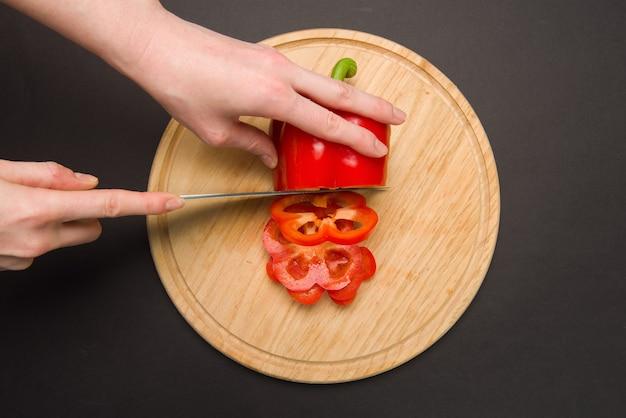 女性は白いプラスチックボード上で赤唐辛子をスライスします。