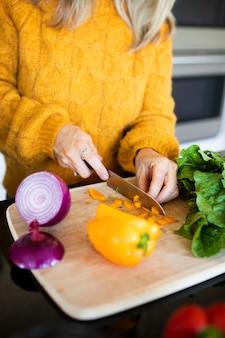 여자 슬라이싱 피망 및 요리 요 주방