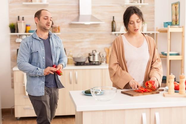 キッチンのまな板でピーマンをスライスする女性。新鮮な野菜を持っている夫。一緒に時間を過ごし、健康的な料理と笑顔で自宅で愛のカップルで面白い幸せ