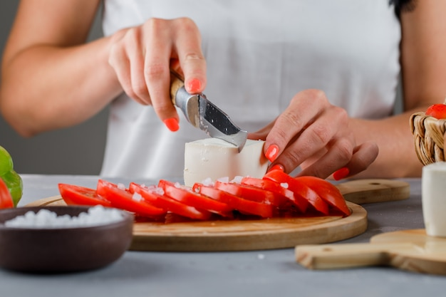 Woman slicing cheese in cutting board with sliced tomatoes, salt on gray surface