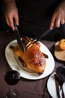 Woman slicing crispy roasted duck on a white plate