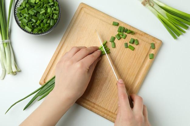 격리 된 흰색 배경에 커팅 보드에 녹색 양파를 자르는 여자