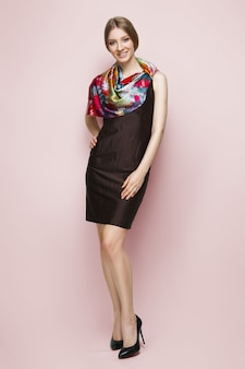 Woman in slim dress and colorful silk scarf posing on pink