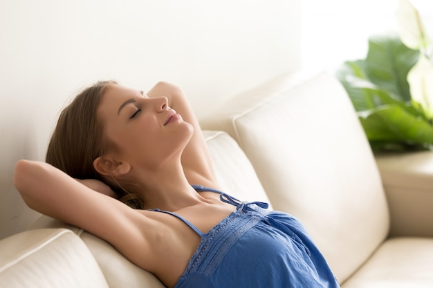 Woman slumbers on couch with hands behind head