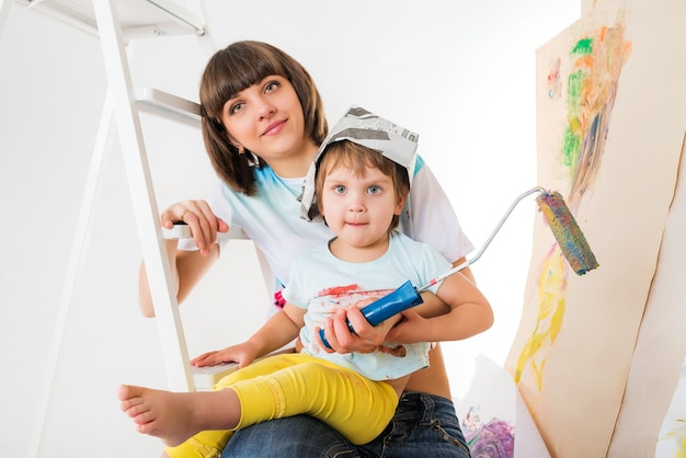 Woman and small child sitting on stepladder and holding tool for painting walls in hands