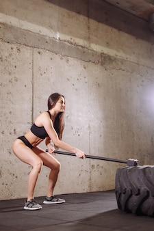 Женщина разбивает большую шину кувалдой во время интенсивной тренировки в спортивном зале