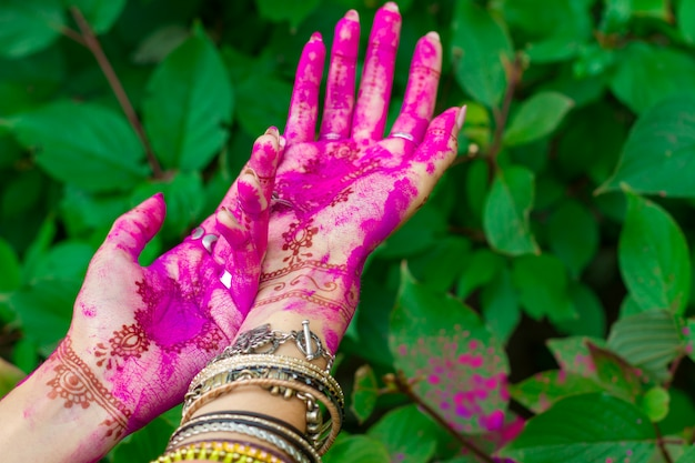 Woman smeared hands with henna tattoo and bracelets jewelry colorful pink violet holi dust powder paint happy traditional indian wedding holiday summer culture festival concept green leaves background