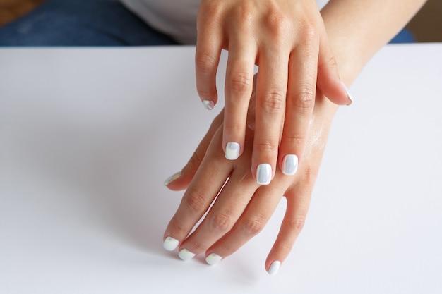 手の肌に柔らかい保湿剤を塗る女性