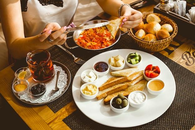 女性は朝食からトーストにバターを塗るトマトバターハニーオリーブチーズトマトキュウリティーレモンジャムサイドビューと卵を設定