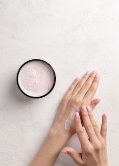 Woman smears hands moisturizing cream white stone background skin care concept    copy space