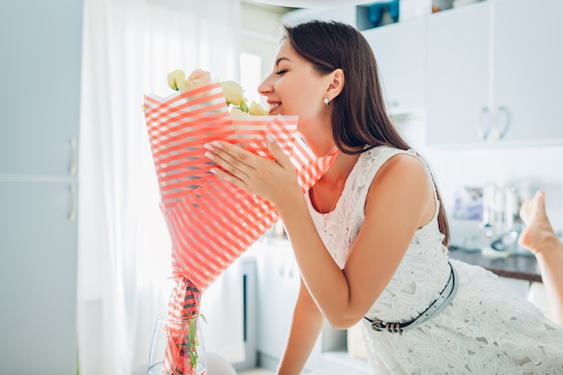 Woman smelling bouquet of flowers at home