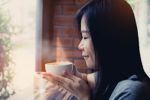Woman smelling and drinking hot tea with happy.