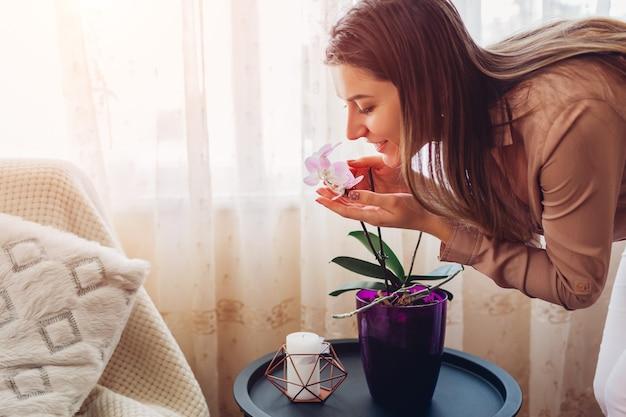 거실에 있는 테이블에 있는 냄비에서 난초 냄새를 맡는 여자. 가정 식물과 꽃을 돌보는 주부. 인테리어 장식