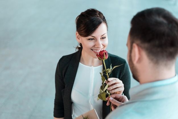 Woman smelling rose given by her boyfriend.