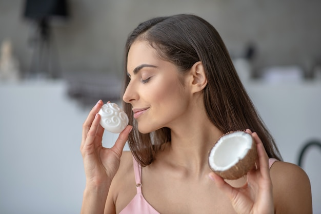 Woman smelling a soap with coconut oil