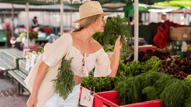Woman smelling some dill from market place