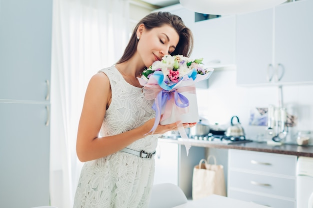 Woman smells bouquet of flowers in gift box on kitchen