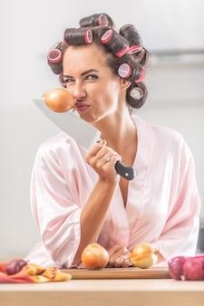 여자는 그녀의 손에 있는 칼에 막대기를 들고 양파 냄새를 맡고 인상을 찡그린다.