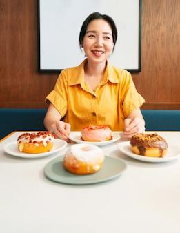 モダンなカフェで、砂糖をまぶしたドーナツの淡い緑色のプレートを持って見せている黄色いシャツを着た女性の笑顔。女性のライフスタイルを楽しんでください。手とドーナツに焦点を当てます。