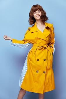 ポケットに女性の笑顔の手黄色の縞模様のコート青い背景