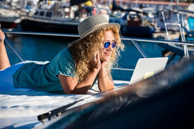 夏休みにボートの甲板に横たわる女性の笑顔とラップトップを見る-自由なライフスタイルの概念現代のきれいな女性-コンピューター技術屋外接続