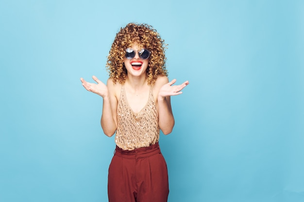 Woman smile red lips curly hair blue background fashion clothes cropped view