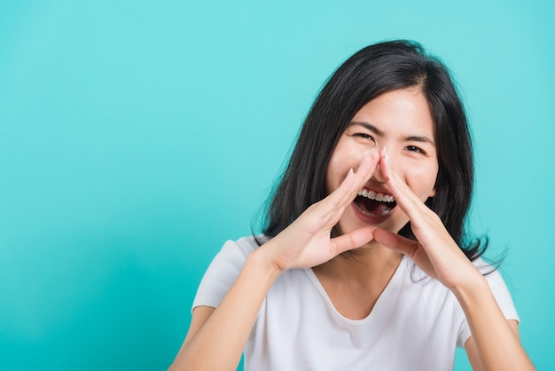 Woman smile wearing white t-shirt and shouting with hands around mouth