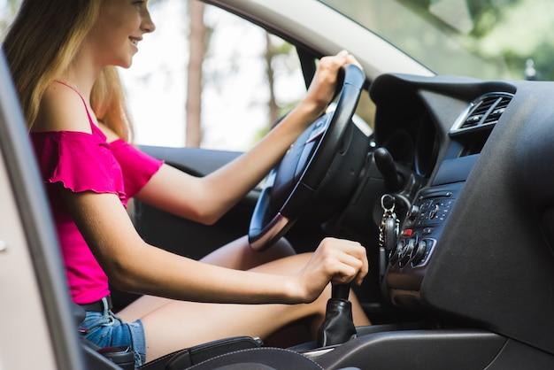 여자는 미소와 운전 방법을 배웁니다