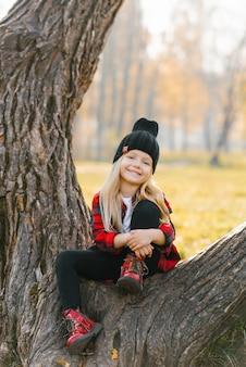 Женщина улыбается, сидя на дереве в осеннем парке в шляпе