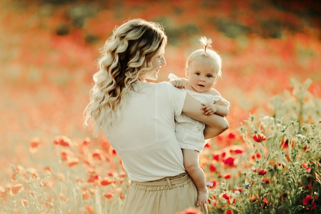 Woman smiles to a baby among flower field