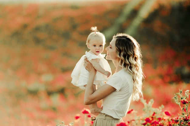 A woman smiles to a baby on the poppy field