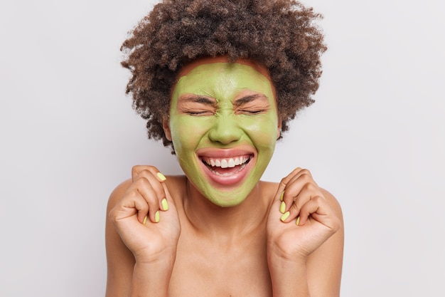 女性の笑顔は広くスキンケアマスクを適用し、手を上げて美容トリートメントを白で隔離します