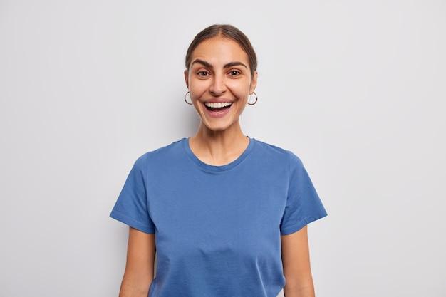 여자 미소는 흰색 캐주얼 파란색 티셔츠를 입고 긍정적인 감정을 광범위하게 표현합니다.
