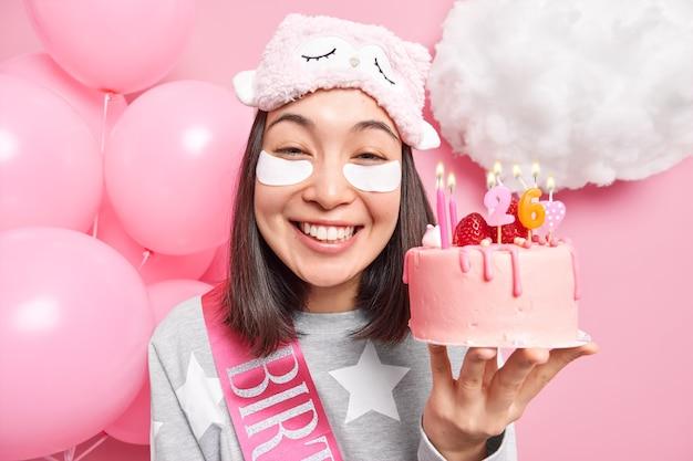 Женщина широко улыбается, держит вкусный торт на день рождения, наслаждается празднованием дома, на вечеринке, одетая в повседневную домашнюю одежду, позирует на розовом