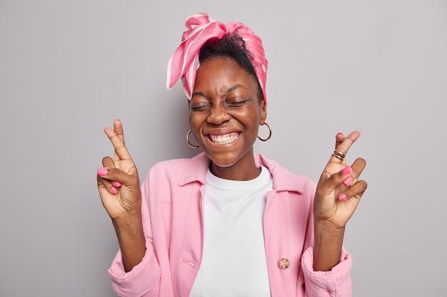 Женщина широко улыбается, показывает белые идеальные зубы, держит пальцы скрещенными, молится и верит в удачу, носит модную розовую куртку с косынкой, повязанную на голове, изолированную на серой стене