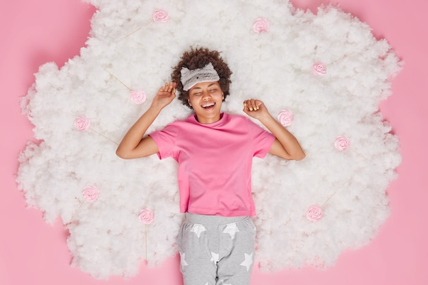 Woman smiles gladfully awakes in good mood feels refreshed and full of energy wears comfortable pajama blindfold on forehead poses on white cloud on pink