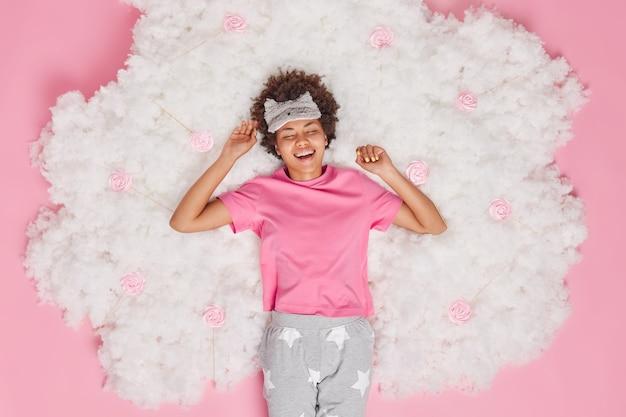Женщина радостно улыбается, просыпается в хорошем настроении, чувствует себя отдохнувшей и полной энергии, носит удобную пижаму с завязанными глазами на лбу, позирует на белом облаке на розовом