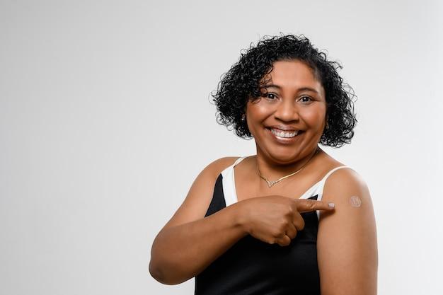 여자는 행복하게 웃으며 팔에 예방 접종을 받았다는 스티커를 보여줍니다